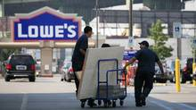 Men leave a Lowe's store with a supply of lumber in New York in this file photo. (Mark Lennihan/AP)