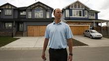 Realtor Jamie Ellice stands in front of boarded up houses in High River, Alta. (JEFF McINTOSH/THE CANADIAN PRESS)
