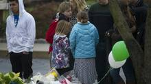 Mourners pay their respect to the victims of the Sandy Hook School shooting at a make-shift memorial created outside Saint Rose of Lima church in Newtown, Conneticut Sunday, Dec. 16, 2012. (Kevin Van Paassen/The Globe and Mail)