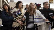 Wrapped in Jewish prayer shawls, Rabbi Susan Silverman, second left, and Hallel Abramowitz, second right, are detained by police officers in Jerusalem's Old City, Feb. 11, 2013. (Tali Mayer/AP)
