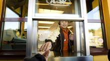 An employee at an A&W in North Vancouver in 2008 gives change back to a costumer. (John Lehmann/The Globe and Mail)