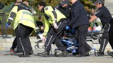Paramedics and police pull a shooting victim away from the Canadian War Memorial in Ottawa on Oct.22. (Adrian Wyld/THE CANADIAN PRESS)