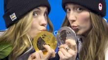 Gold medal winner Justine Dufour-Lapointe and her silver medal winning sister Chloe Dufour-Lapointe, show their medals on Feb. 9, 2014. (John Lehmann/The Globe and Mail)