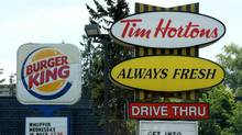 A Burger King sign and a Tim Hortons sign are displayed on St. Laurent Boulevard in Ottawa in this file photo. (Sean Kilpatrick/THE CANADIAN PRESS)