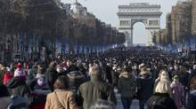 Parisians stroll along the Champs-Elysee avenue prior to a New Year's Day parade in Paris, Thursday, Jan. 1, 2015. (Michel Euler/AP)