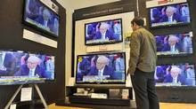 A man watches televisions in a shop in Glasgow, July 19, 2011. (ANDY BUCHANAN/ANDY BUCHANAN / AFP/Getty Images)