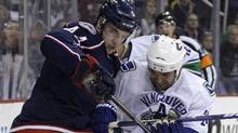 Columbus Blue Jackets' Grant Clitsome, left, and Vancouver Canucks' Darcy Hordichuk fight for a loose puck during the first period of an NHL hockey game Tuesday, March 2, 2010, in Columbus, Ohio. (Jay LaPrete/Associated Press)