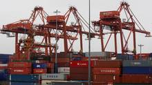 Cargo containers are stacked up as three cranes used to load and unload them from cargo ships tower above at the Port of Vancouver in Vancouver, B.C. (DARRYL DYCK/Darryl Dyck/The Canadian Press)