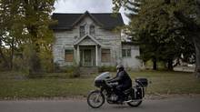 Reporter Patrick Martin rides through Flint, Mich., on his motorcycle. The city whose decline was featured in the 1989 film Roger & Me has descended even further into unemployment and crime. (Moe Doiron/The Globe and Mail)