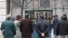 People look at stock market indexes on a monitor outside a bank in Milan in this file photo. Unicredit, Italy's biggest bank, is cutting 1,000 jobs at its German unit, sources say. (Antonio Calanni/AP)