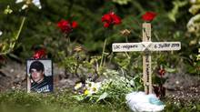A photograph of one of the missing, Kevin Roy, 29, leans against a flower after being placed their by his mother, Lise Doyon, and her partner, Jeannot Labreque. (Peter Power/The Globe and Mail)