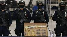 """Mexican federal police officers stand guard behind an AK-47 rifle and ammunition, confiscated during the arrest of suspect Ramiro Pozos Gonzalez, alias """"El Molca"""", a suspected leader and founder of the criminal organization known as The Resistance, during a presentation to the media at the federal police headquarters in Mexico City on Sept. 12, 2012. (Bernardo Montoya/REUTERS)"""
