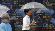 A man walks by an electronic stock indicator in Tokyo on Aug. 6, 2012. Asian stock markets rose sharply in early trading Monday, boosted by stronger-than-expected U.S. hiring figures for July following three months of weak job gains. (Shizuo Kambayashi/AP)