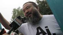 Activist artist Ai Weiwei opens the gate to talk to journalists gathered outside his home in Beijing, China, Thursday, June 23, 2011. (Ng Han Guan/AP)