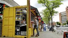 Vendors sell food out of shipping containers that have been transformed into micro-stores outside of the Scadding Court Community Centre in Toronto on May 30, 2012. (Peter Power/The Globe and Mail/Peter Power/The Globe and Mail)