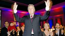 Quebec Liberal party leader Jean Charest waves to supporters as his wife Micha�le Dionne looks on at a Liberal party council general meeting in Saint Hyacinthe, Que., Sunday, April 18, 2010. (Graham Hughes/THE CANADIAN PRESS)