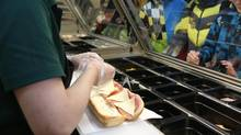 An employee prepares a customer's sandwich order at the food counter of a Subway fast food restaurant on Sunday, April 7, 2013. (Andrey Rudakov/Bloomberg)