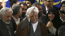 Former Iranian president Hashemi Rafsanjani waves to reporters as he registers his candidacy for the upcoming presidential election, at the election headquarters of the interior ministry in Tehran on May 11, 2013. (Ebrahim Noroozi/Associated Press)