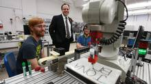 Mohawk College president Ron McKerlie, centre, talking with Tyler Facchini, left, and Jonathon Brunathin in a robotics lab, says his school can't keep up with demand for skilled-trades grads. (Glenn Lowson for The Globe and Mail)