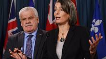 Chris Aylward, PSAC National Executive vice-president listens as Debi Daviau, PIPSC president, speaks during a news conference in Ottawa on Feb. 23, 2017. (Adrian Wyld/THE CANADIAN PRESS)