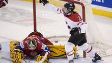 Canada's Meghan Agosta-Marciano celebrates a goal from Haley Irwin as Russian goalie Anna Prugova flops helplessly. (Adrian Wyld/THE CANADIAN PRESS)