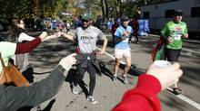Runners are handed water by supporters during a fun run in New York's Central Park, November 4, 2012. (Chip East/Reuters)