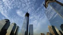 One World Trade Center, centre, rises above the National September 11 Memorial and Museum at the World Trade Center, Thursday, Sept. 6, 2012 in New York. Tuesday will mark the eleventh anniversary of the terrorist attacks of Sept. 11, 2001. The World Financial Center is on the left, and Four World Trade Center is at right. (Mark Lennihan/AP)