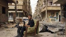 A member of the Free Syrian Army holds his weapon as he sits on a sofa in the middle of a street in Deir al-Zor, in this April 2, 2013, file photo. The United States believes with varying degrees of confidence that Syria's regime has used chemical weapons on a small scale, the White House said last Thursday. (STRINGER/REUTERS)