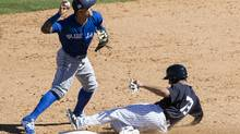 Toronto Blue Jays' Christian Lopes attempts a double play after New York Yankees' Francisco Diaz is forced out during a spring training baseball game on Feb. 26, 2017. (Matt Rourke/AP)