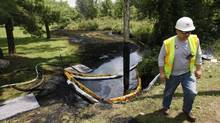 In this file photo, a worker monitors the water in Talmadge Creek in Marshall Township, Mich., near the Kalamazoo River as oil from a ruptured pipeline, owned by Enbridge Inc., is vacuumed out the water. A pipeline rupture spilled more than 800,000 gallons of crude oil into the river nearly two years ago. Today's topics: Enbridge's failures; the minister and the visa; blame corporatism, not collegialism; copyright time-out … and more (Paul Sancya/AP)