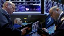 Traders gather at the post where Valeant Pharmaceuticals is traded on the floor of the New York Stock Exchange. (BRENDAN MCDERMID/REUTERS)