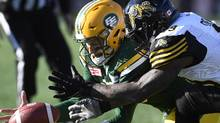 Edmonton Eskimos' Mike Reilly dives for a loose ball with the Hamilton Tiger Cats' Larry Dean during CFL playoff action on Nov. 13, 2016. (Frank Gunn/The Canadian Press)