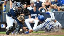 Toronto Blue Jays second baseman Munenori Kawasaki scores on a base hit by shortstop Jose Reyes (not pictured) as the ball gets away from Milwaukee Brewers catcher Jonathan Lucroy in the fifth inning at Miller Park. (Benny Sieu/USA Today Sports)