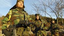 South Korean marines stand guard on Nov. 26, 2010, at a check point on Yeonpyeong Island, which was shelled by North Korea. (JO YONG-HAK/REUTERS)