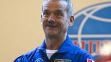 The International Space Station crew member Canadian astronaut Chris Hadfield reacts during a news conference behind a glass wall at the Baikonur cosmodrome December 18, 2012. (SHAMIL ZHUMATOV/REUTERS)