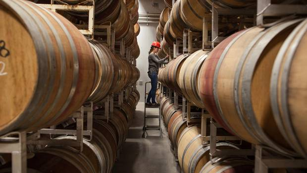 Katlyn Wise, the cellar technician, takes a sample from the barrels for lab analysis at Time Winery in Penticton, B.C.
