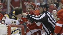 A referee breaks up Boston Bruins left wing Jordan Caron (38) and Detroit Red Wings left wing Justin Abdelkader during the first period of Game 3 of a first-round NHL hockey playoff series in Detroit, Tuesday, April 22, 2014. (Carlos Osorio/THE ASSOCIATED PRESS)