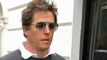 Hugh Grant leaves his home in west London in 2007 under the gaze of the paparazzi. (Ian West/Ian West / AP)