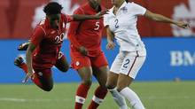 Canada defender Robyn Gayle looks on as Kadeisha Buchanan is fouled by USA's forward Sydney Leroux during a friendly match in Winnipeg last May. (JOHN WOODS/THE CANADIAN PRESS)