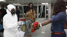 A passenger holds personal possessions as a Nigerian port health official uses a thermometer on her at the arrivals hall of Murtala Muhammed International Airport in Lagos, Nigeria, Wednesday Aug. 6, 2014. (Sunday Alamba/AP)