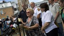 Mayor Colette Roy-Laroche gives a press conference in Lac-Mégantic, PQ on July 13, 2013. The railroad tracks lead to the site of this tragedy, beyond the fencing at right. (Peter Power/The Globe and Mail)