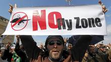 An anti-Libyan leader Moammar Gadhafi protester, holds a sign during a protest after the Friday prayer at the Court Square, in Benghazi, eastern Libya, on Friday March 11, 2011. (Hussein Malla/The Associated Press/Hussein Malla/The Associated Press)