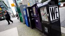 A woman walks past free newspaper boxes in downtown Vancouver, B.C., on Thursday March 29, 2012. (DARRYL DYCK For The Globe and Mail)