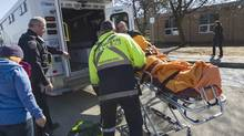A student is wheeled out of Dunbarton High School and placed in an ambulance following a stabbing at the Pickering, Ont., school on Feb. 23. (J.P. MOCZULSKI/The Globe and Mail)