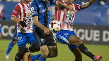 Montreal Impact's Andrew Wenger, left, and CD Heredia's Henry Medina battle for the ball during first half CONCACAF champions league action in Montreal, Tuesday, September 24, 2013. (Graham Hughes/THE CANADIAN PRESS)