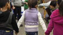 Mariah Al Rassoul, centre, holds hands with classmates Aarush, left, and Kaili during her first day in kindergarten on Jan 4. (Fred Lum/The Globe and Mail)