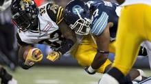 Toronto Argonauts defensive lineman Ivan Brown (right) tackles Hamilton Tiger-Cats running back C.J. Gable during first half CFL action in Toronto on Friday October 4, 2013. Tiger-Cats running back C.J. Gable has been named the CFL player of the week. (FRANK GUNN/THE CANADIAN PRESS)