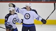 Winnipeg Jets defenceman Paul Postma (R) celebrates his goal against the Columbus Blue Jackets with teammate Janne Pesonen during the first period of NHL pre-season action in Winnipeg September 20, 2011. (FRED GREENSLADE/REUTERS)