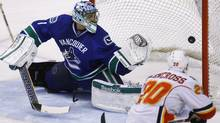 Calgary Flames' Curtis Glencross scores on Vancouver Canucks goaltender Roberto Luongo (L) during the third period of their NHL game in Vancouver, British Columbia December 23, 2011. REUTERS/Ben Nelms (Ben Nelms/Reuters)