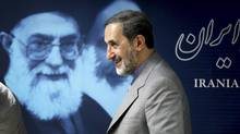 Iranian presidential candidate Ali Akbar Velayatiwalks past a portrait of supreme leader Ayatollah Ali Khamenei after a press conference in Tehran on Monday, June 3, 2013. The 11th presidential election after Iran's 1979 Islamic Revolution will be held on June 14. (Ebrahim Noroozi/Associated Press)